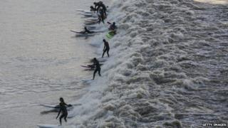Surfers riding the Severn Bore in Newnham