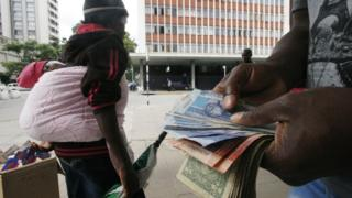 Someone holding South African rand and US dollars in Zimbabwe's capital, Harare