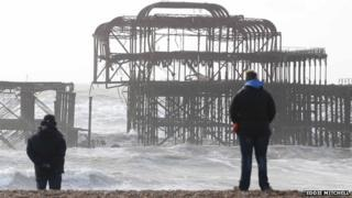 People looking at the new damage to the pier