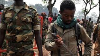 A government soldier puts his knife away after allegedly taking part in the lynching in Bangui. Photo: 5 February 2014