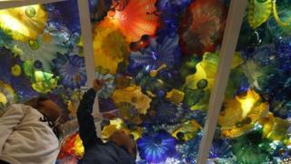 Two children pose underneath a glass sculpture by US artist Dale Chihuly at the Halcyon Gallery in London