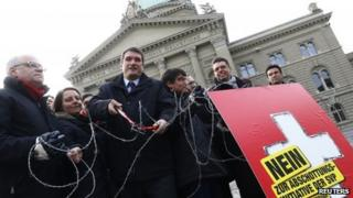 A Swiss Socialist Party member and others cut a symbolic barbed wire fence, as part of their campaign to re-impose quotas on migrants