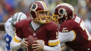 Washington Redskins quarterback Kirk Cousins looks for an opening to pass during the first half of an NFL football game against the Dallas Cowboys in Landover, Maryland, on 22 December 2013