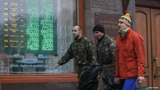 Anti-government demonstrators walk past a currency exchange office in Kiev February 7, 2014.