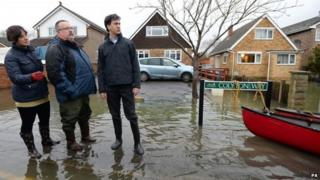 Labour leader Ed Miliband (right) and Victoria Groulef (left), Labour's Parliamentary Candidate for Reading West, with local resident Adrian North (centre) during a visit to the view recent flooding in Purley on Thames in Berkshire.