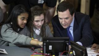 George Osbourne with two schoolgirls looking at a small computer