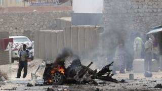 Security personnel gather at the scene of an explosion near the entrance of the airport in Somalia's capital Mogadishu -13 February 2014