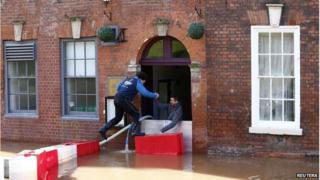 Men climb in to a restaurant surrounded by flood waters in Worcester