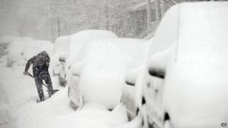 A woman digs her car out of the snow on 15th Street in Bayonne, New Jersey 13 February 2014