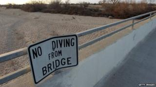 "A ""no diving"" sign hangs on a bridge over the dry Kern River near Los Angeles, California."
