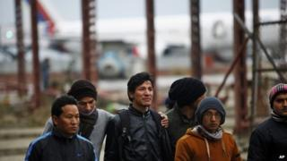 A Nepalese man consoles a relative, center, of a missing passenger