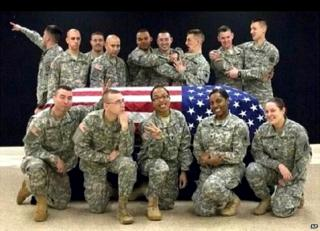 This photo posted to the Instagram account belonging to Spc Terry Harrison shows a dozen soldiers clowning around a coffin draped in a flag at a National Guard training facility in Arkansas