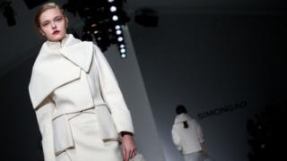 Models present creations for the Simongao collection during the 2014 Autumn / Winter London Fashion Week in London