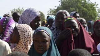 A woman wipes away tears at a refugee camp for people displaced by violence in Borno state, Nigeria