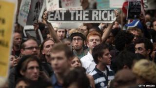 "A Occupy Wall Street protestor holds up a sign reading ""eat the rich"" in September 2011."