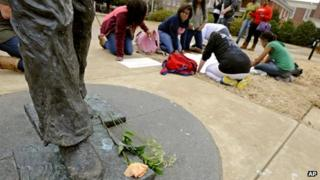 A flower rests at the foot of the James Meredith statue as students make signs during protest at the University of Mississippi in Oxford, Mississippi, on 18 February 2014