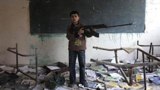 Boy with a toy gun in damaged school in Deir al-Zor, Syria
