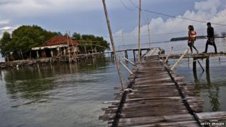 Villagers walk over bamboo bridges in central Java