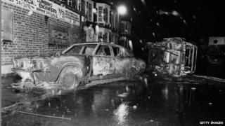 Cars left overturned and burned-out in the street after rioting on the Broadwater Farm housing estate