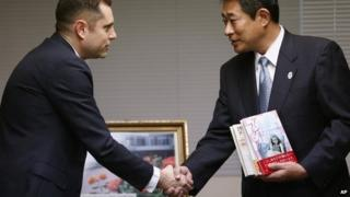 Israeli Embassy to Japan representative Peleg Lewi, left, shakes hands with Suginami Ward Mayor Ryo Tanaka as he hands over Anne Frank-related books to public libraries at the Suginami Ward Office in Tokyo Thursday, Feb. 27, 2014