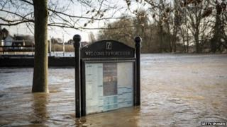 A tourist information sign surrounded by water