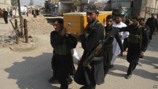 Pakistani security personnel carry the body of a fellow officer who was killed in a bomb blast