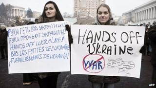 "Two women hold banners reading ""hands off Ukraine"" in different languages, in Kiev's Independence Square"