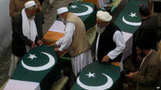 Relatives of Pakistani police officers killed in Saturday's attack prepare their coffins, near Peshawar (1 March)