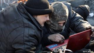 Anti-government protesters read the latest news on internet at a barricade in Kiev