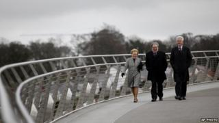 """Former US President Bill Clinton walks with former Social Democratic Labour Party leader John Hume and Hume""""s wife Pat across the Peace Bridge, in Londonderry"""