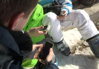 Three men in ski boots look at smartphones