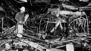 A fireman hoses down smouldered debris inside the Debenhams store at Luton, Befordshire