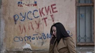 "A woman passes by graffiti that reading ""The Russians are coming - Resistance"" in Simferopol, Crimea"