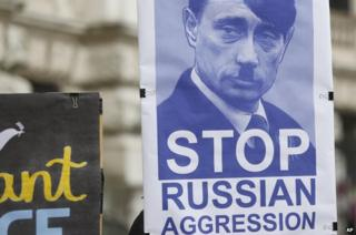 Activists hold a poster featuring Russian President Vladimir Putin as Hitler during a protest in Vienna, 3 Mar 14
