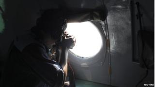 A Vietnamese Air Force officer takes photos from a search and rescue aircraft, 250km from Vietnam and 190km from Malaysia, 8 March