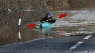 A man paddles his canoe down a flooded road in Somerset