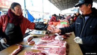 Man and woman at market in China with meat