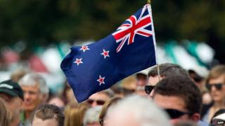 A man holds a New Zealand flag at a ceremony in Christchurch on 22 February 2012