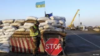 A Ukrainian soldier mans a checkpoint near the village of Salkovo, near the Ukrainian border with the Crimean region