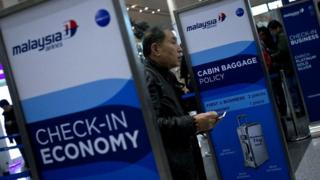 A man presents his passport at a Malaysia Airways check-in counter in Beijing