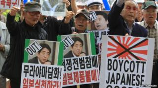 South Korean hold placards carrying the images of Japanese Prime Minister Shinzo Abe and Osaka Mayor Toru Hashimoto during a rally on May 23, 2013 in Seoul