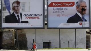 A child rides a toy bike in front of smeared placards featuring populist leader Aleksandar Vucic and former president Boris Tadic in Belgrade, Serbia, on 14 March 2014.
