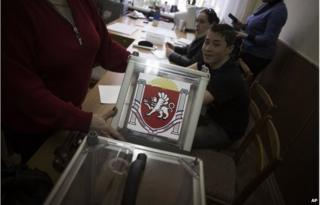 A Ukrainian election official holds a ballot box during preparations for Sunday's referendum at a polling station in Simferopol, Ukraine, March 15