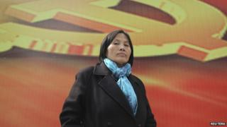 Prominent Chinese human rights activist Cao Shunli stands in front of an emblem of the Chinese Communist Party during an interview in the central business district of Beijing March 23, 2013