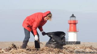 Woman collecting rubbish on beach