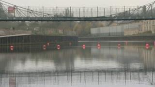 Bright orange buoys stop river traffic from sailing underneath the Victoria Bridge on the River Avon in Bath
