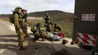 A wounded Israeli soldier is prepared for evacuation by medics near the town of Majdal Shams (18 March 2014)
