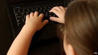 Child using a computer (posed by model)
