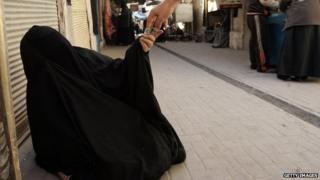 A woman in a burqa begging