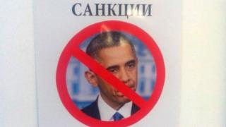 "An sign which says ""sanctions"" and has an image of Barack Obama with a cross through it"